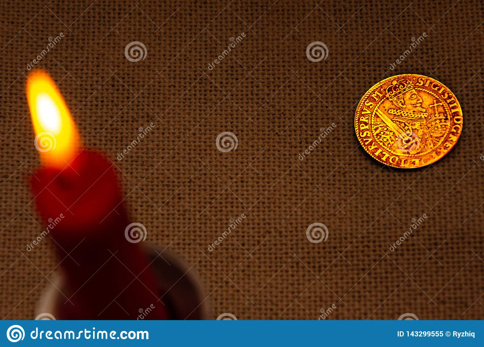 Ancient silver coin and burning candle