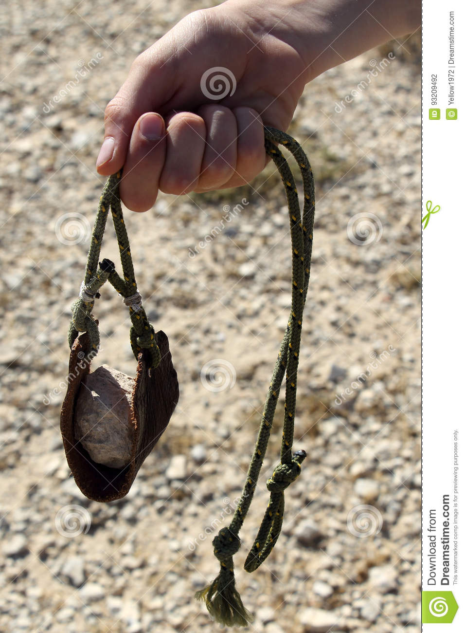 Hand Throwing Stone : Ancient weapon sling for stone throwing stock photo