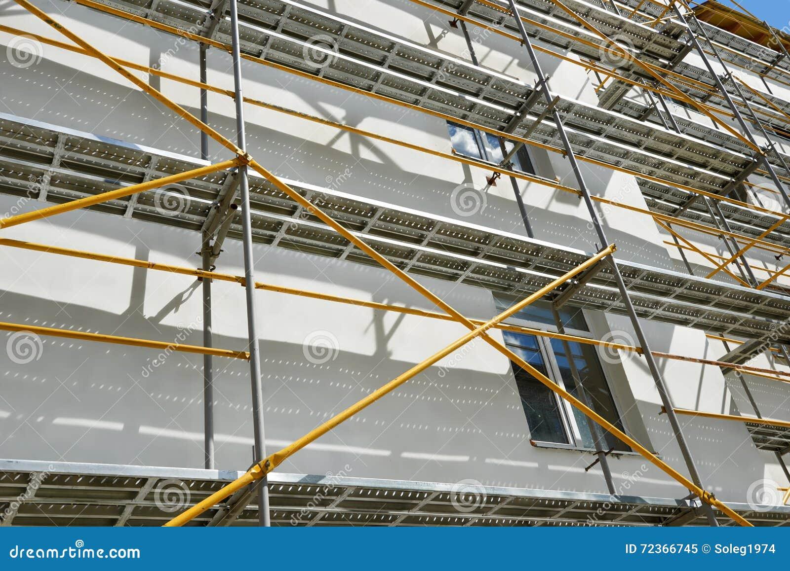 Andaime perto de uma casa sob a construção para trabalhos externos do emplastro, o prédio de apartamentos alto na cidade, a pared