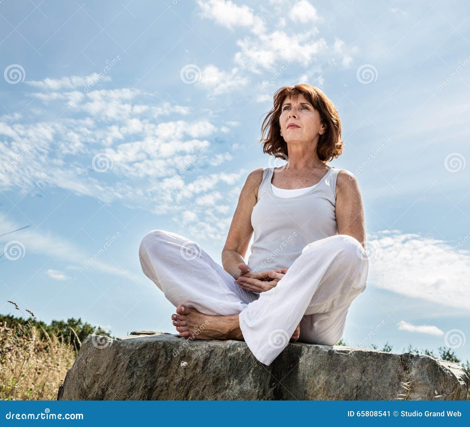 Andning för härlig mitt åldrades utomhus yogakvinnan