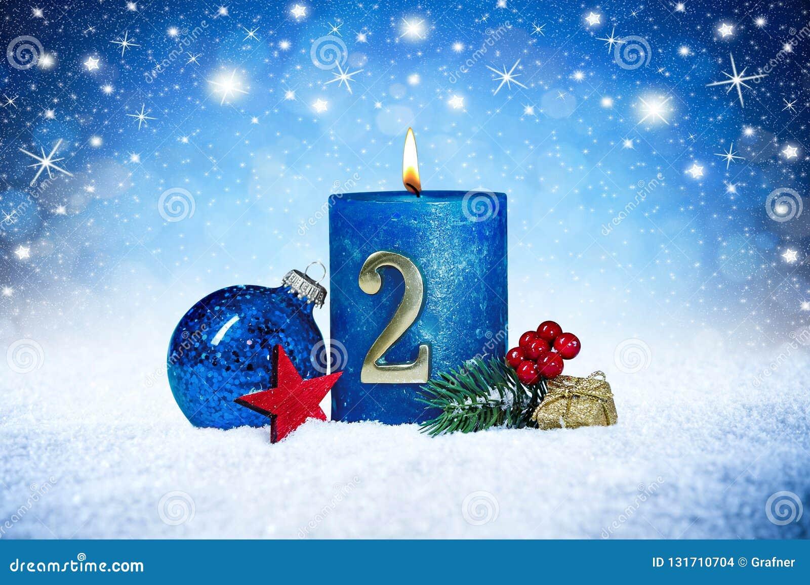 Andra söndag av den blåa stearinljuset för advent med röd garnering en för guld- metallnummer på träplankor i snöframdel av silve
