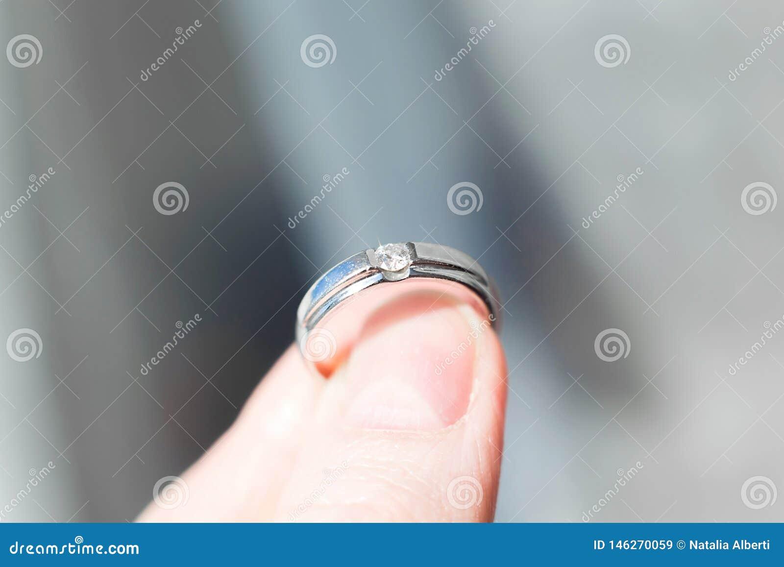 Anel com o brilhante nos dedos