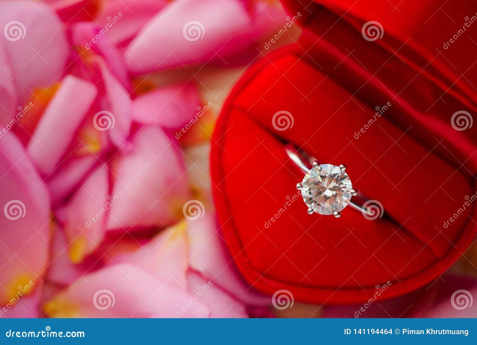 Anel de diamante elegante do casamento na guarda-joias vermelha do coração no fundo cor-de-rosa bonito da pétala cor-de-rosa