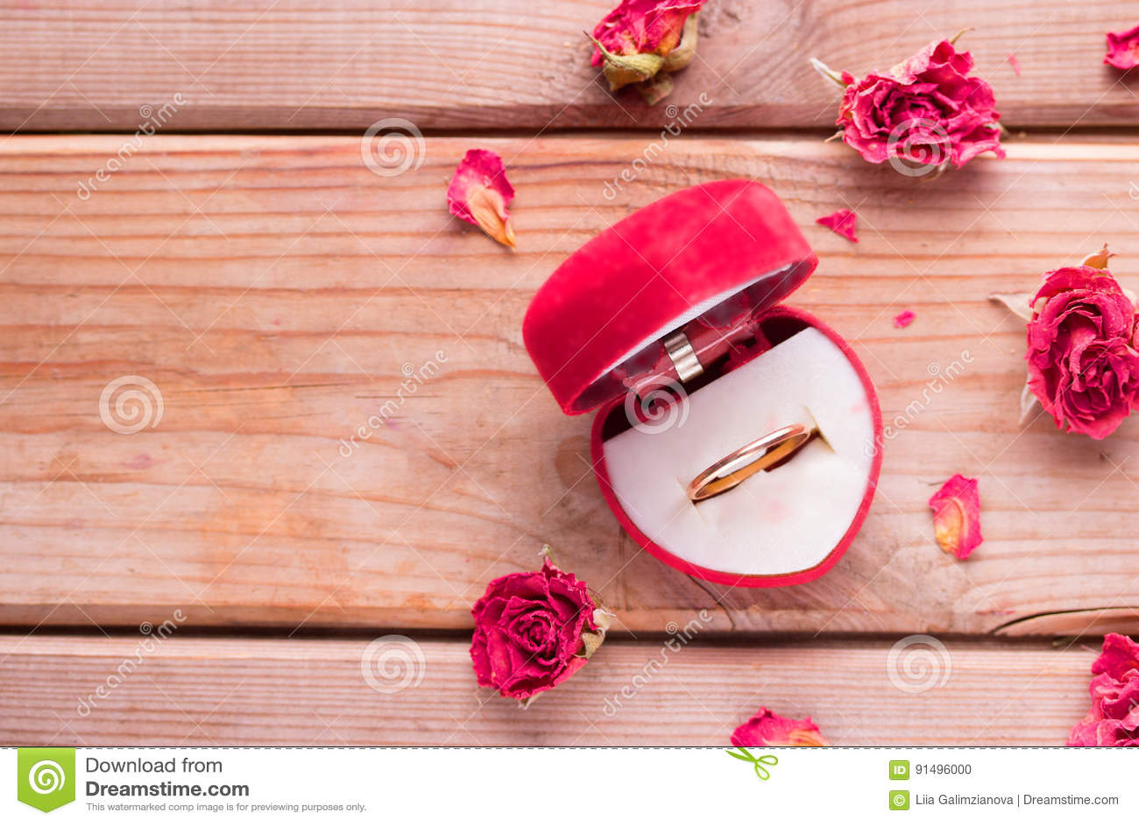 Anel de noivado dourado em uma caixa dada forma coração