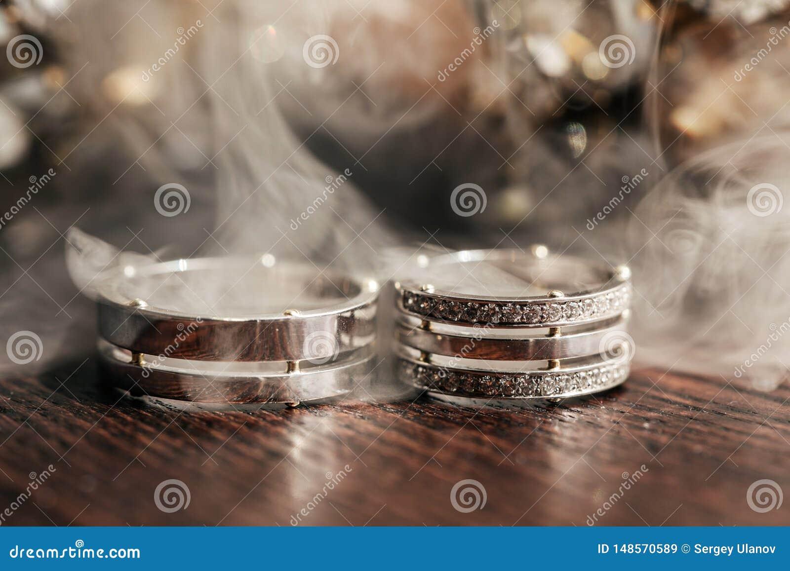 Anelli bianchi di nozze sulla tavola con fumo
