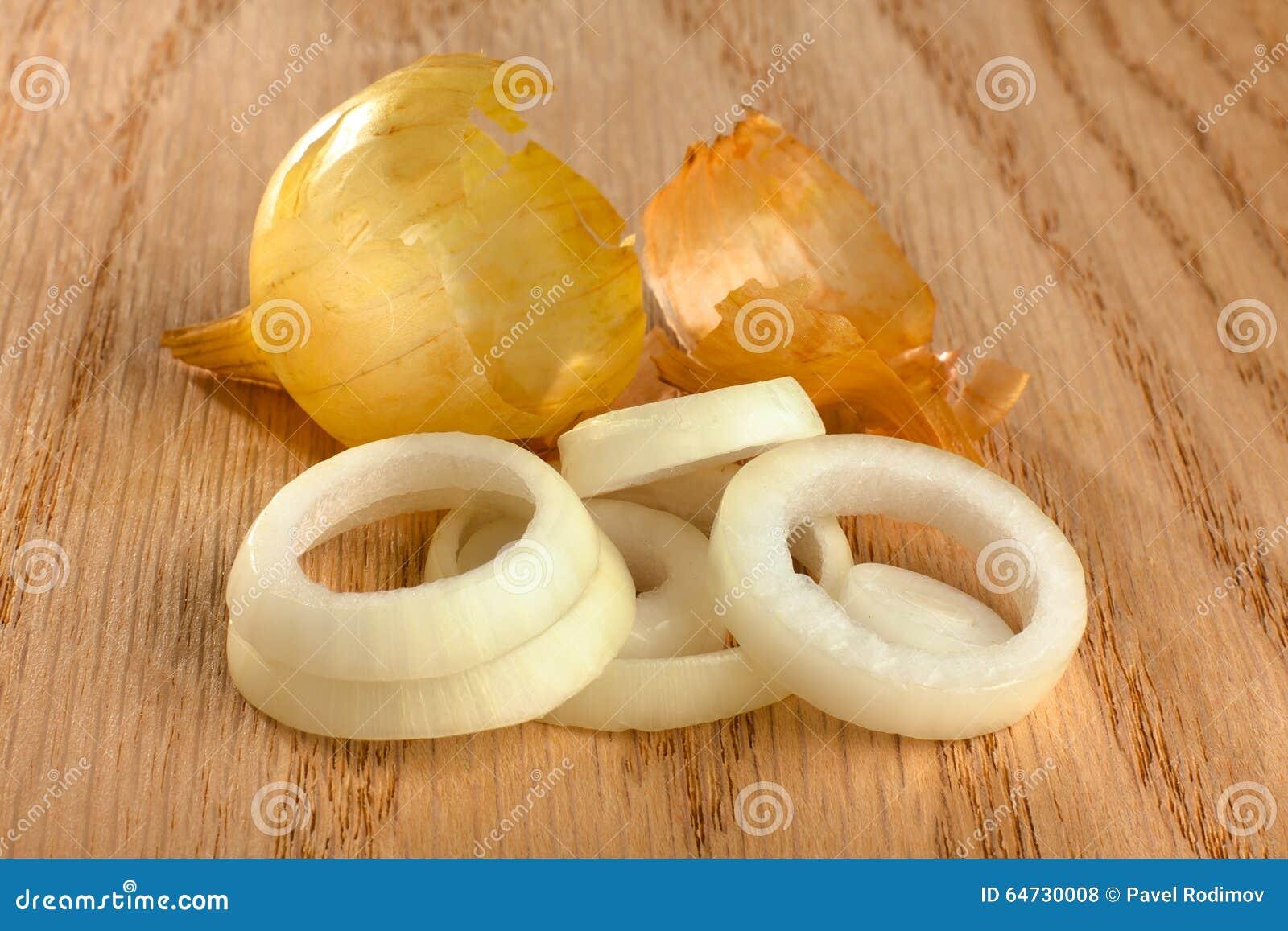 Anelli della cipolla con la buccia su fondo di legno