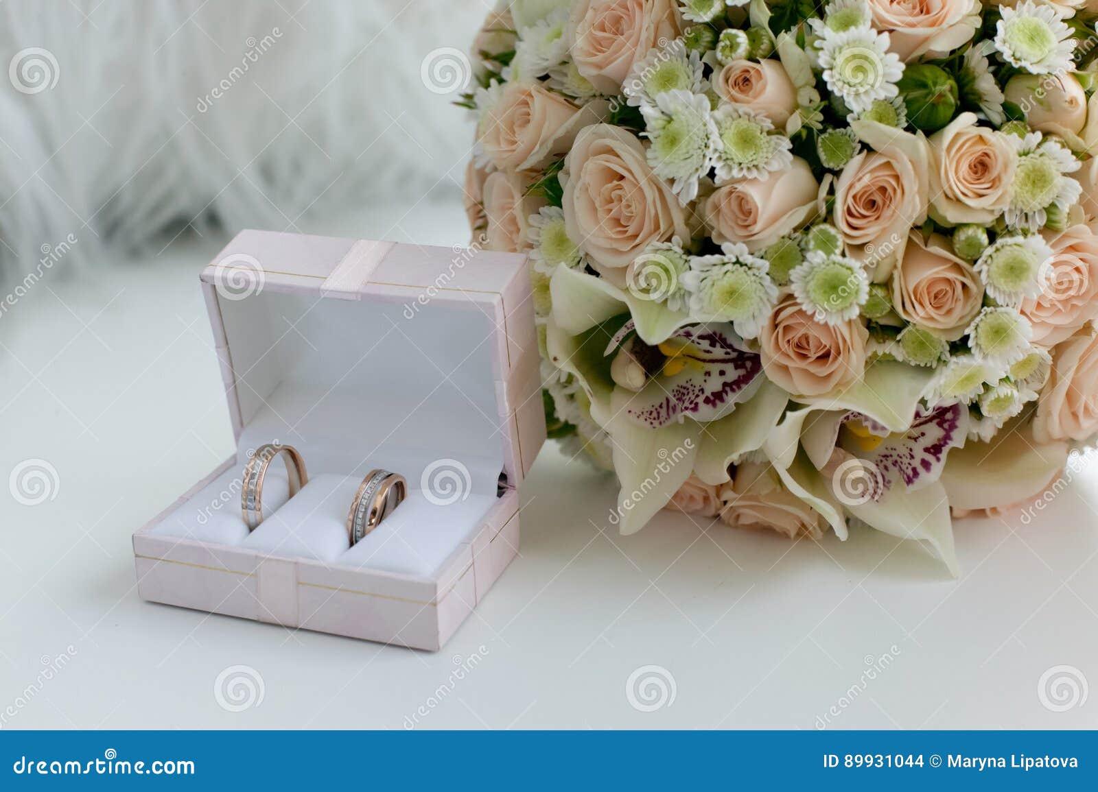 Anelli della sposa e dello sposo di nozze in una scatola sulla tavola