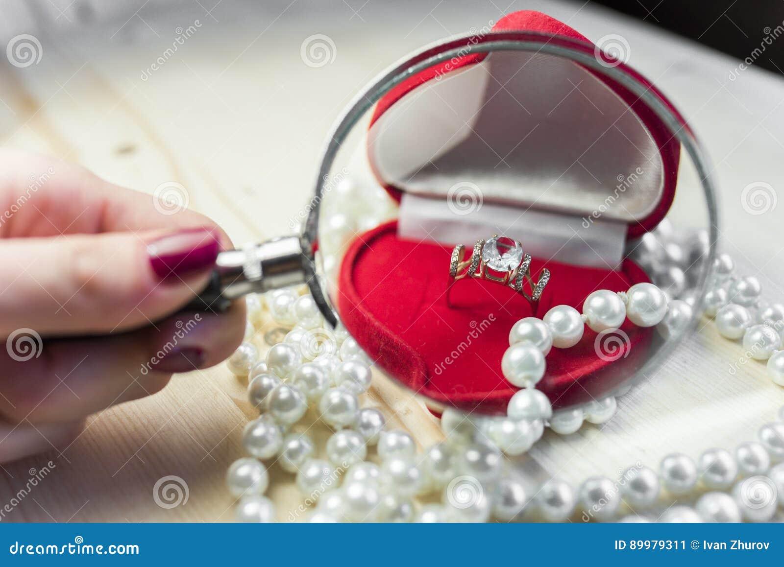 Anello dorato con topazio in un contenitore di regalo rosso con le perle sull orlo della tavola