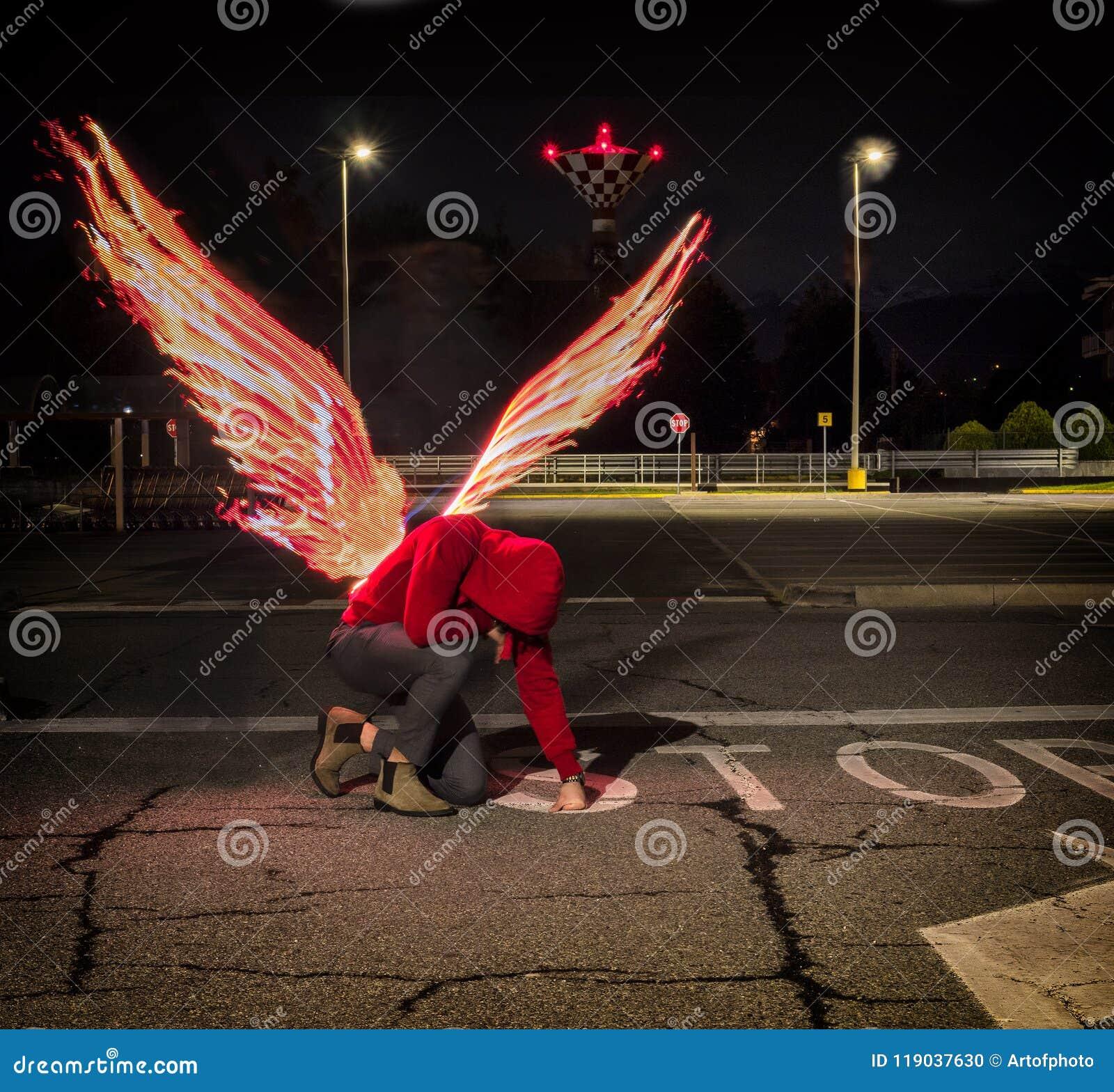 Ange masculin tombé avec des ailes du feu