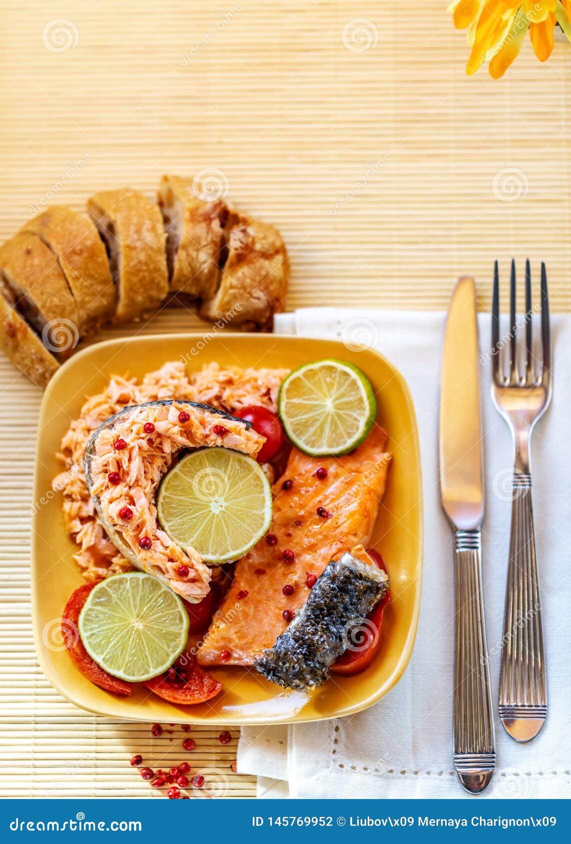 Angefüllt fischen Sie einen Lachs mit Scheiben einer Zitrone oder des Kalkes auf einer Platte