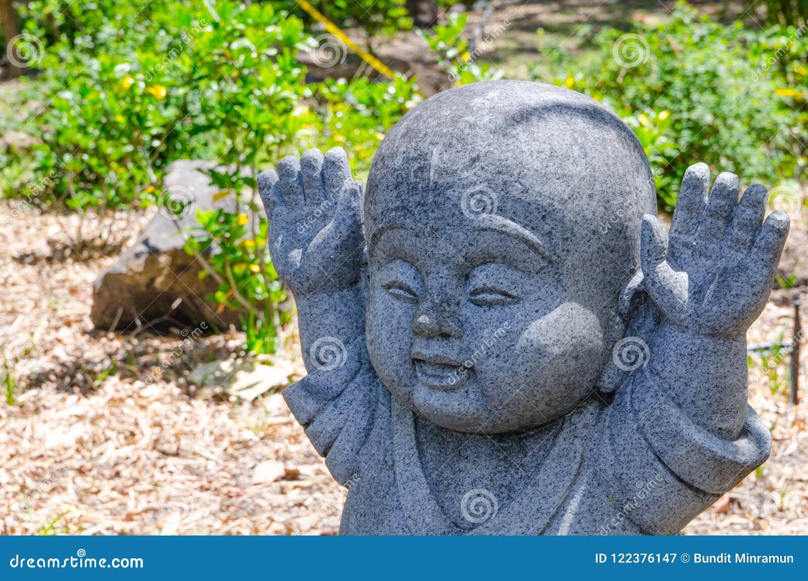 Angehobene Hände up Bewegung von Jizo wenig Stein-Buddha-Statue