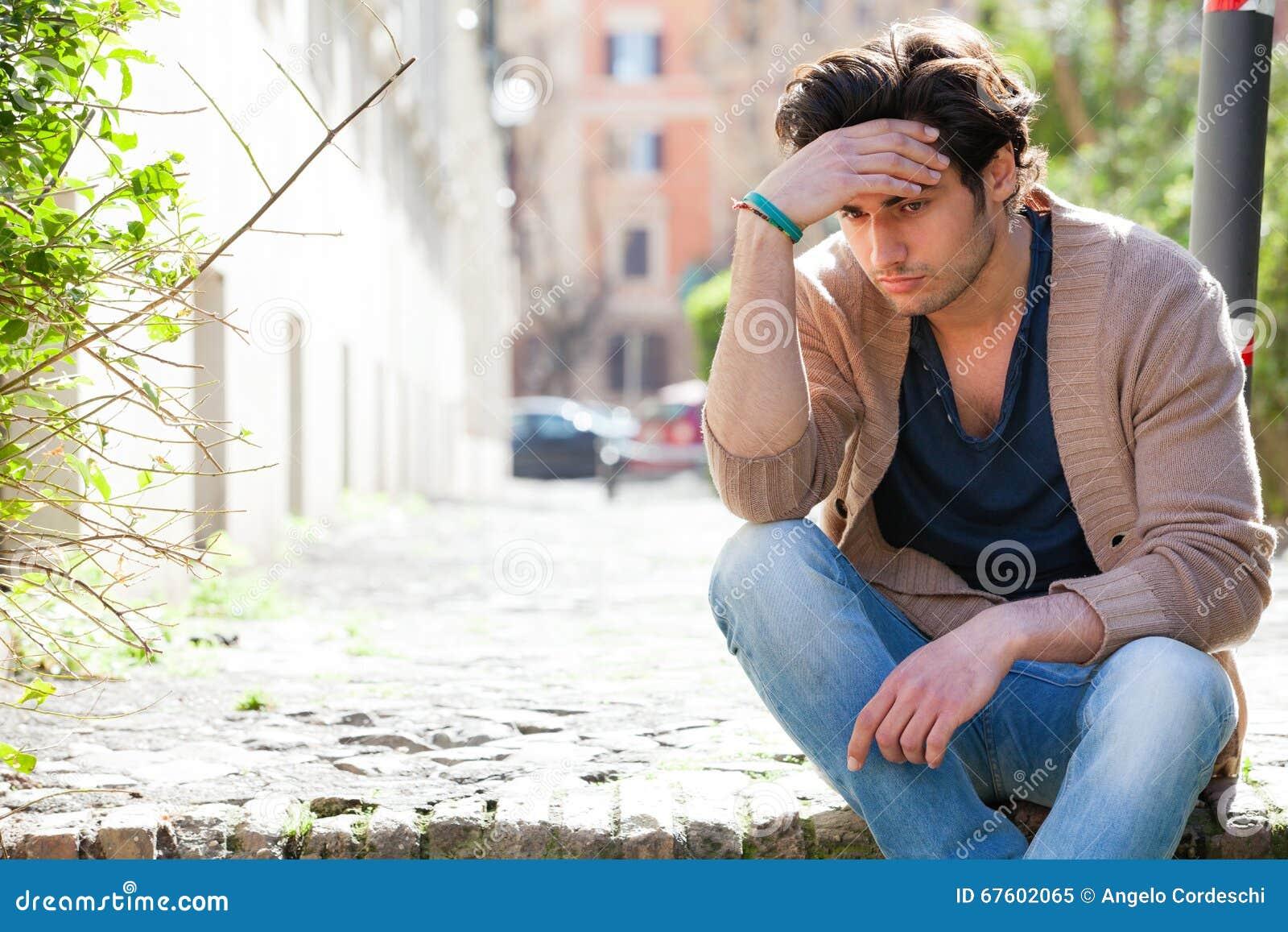 _ Angelägen fundersam ung man, utomhus