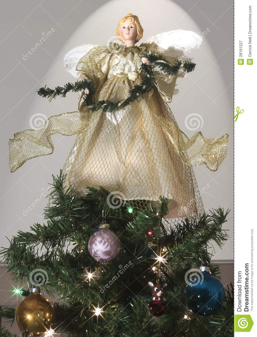 An angel atop a decorated christmas tree stock image