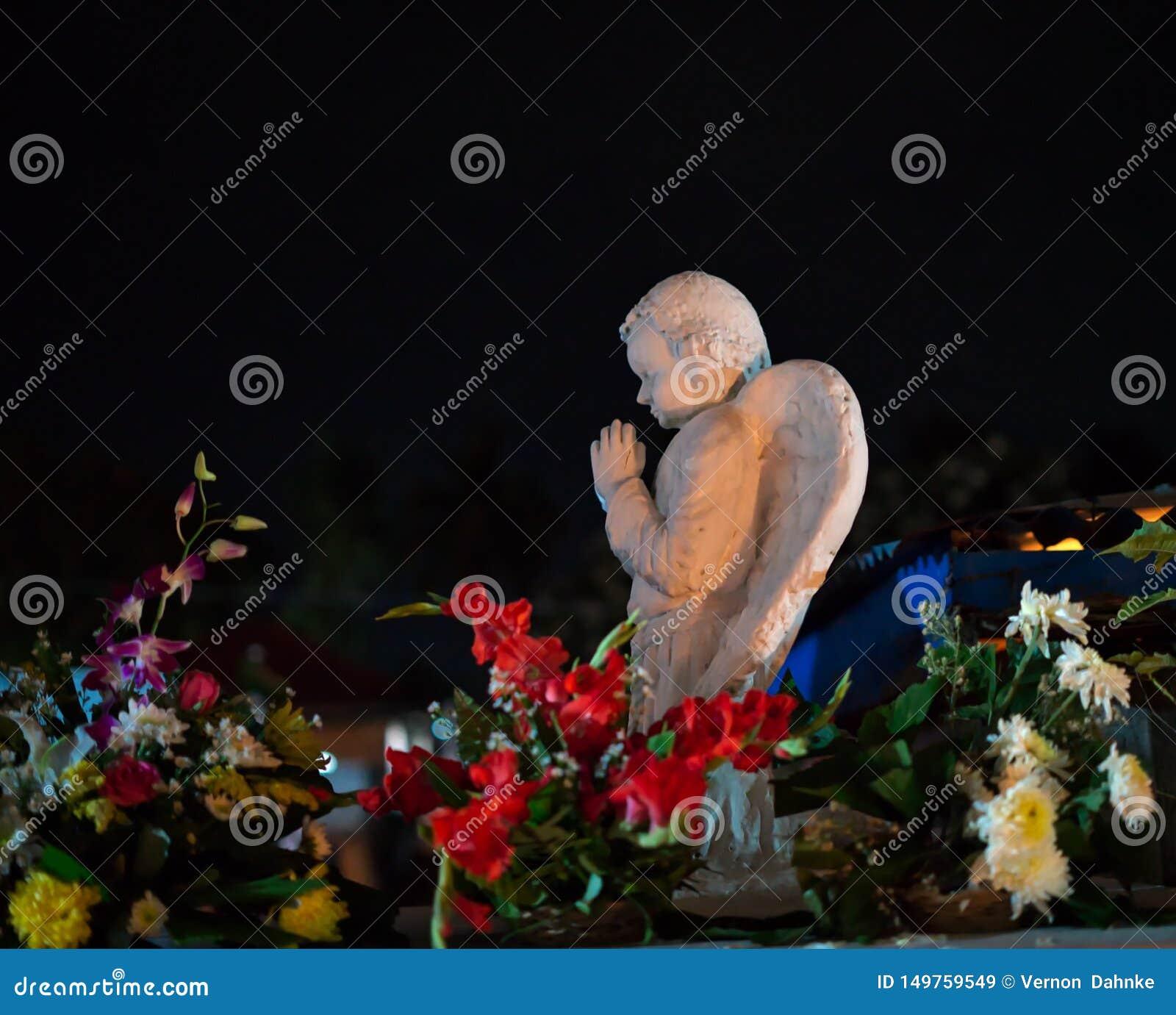 Angelo variopinto di scena di notte che prega in cima ad una tomba