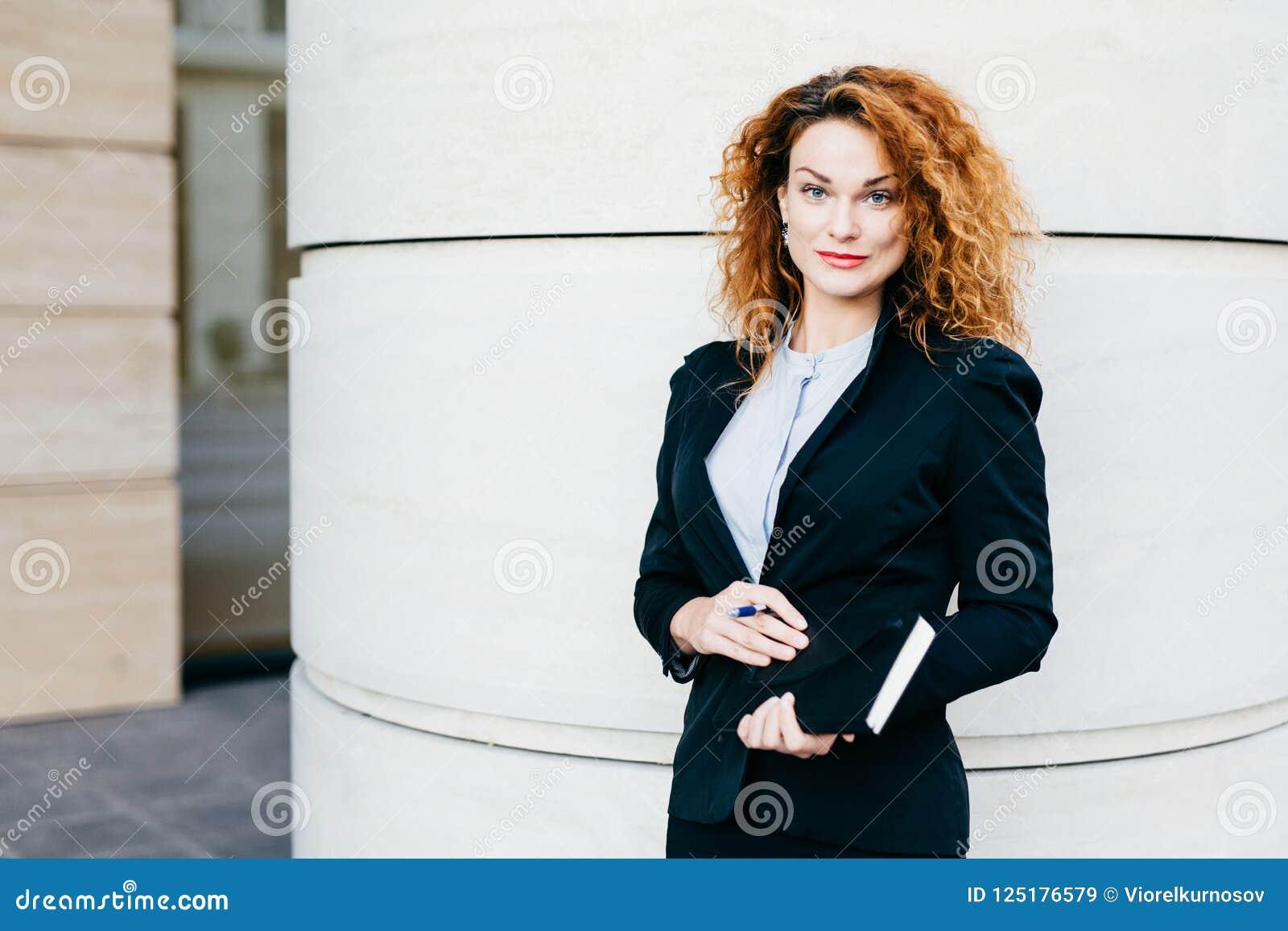 Angenehm-aussehende gelockte Frau kleidete formal an und hielt Notizbuch in den Händen und ging, Sitzungsesprit zu haben ihre Tei