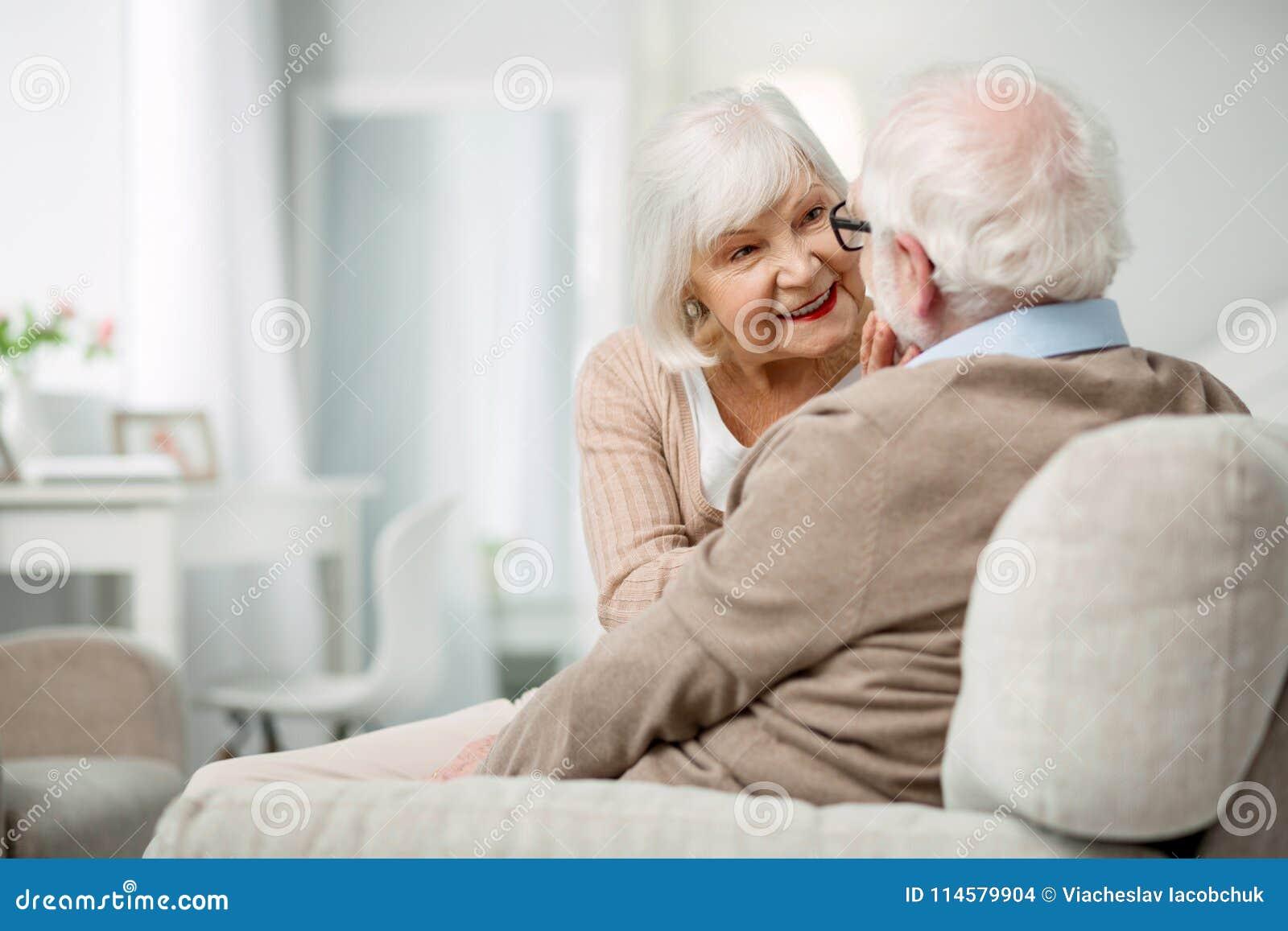 Angenehme ältere Frau, die ein Gespräch mit ihrem Ehemann hat
