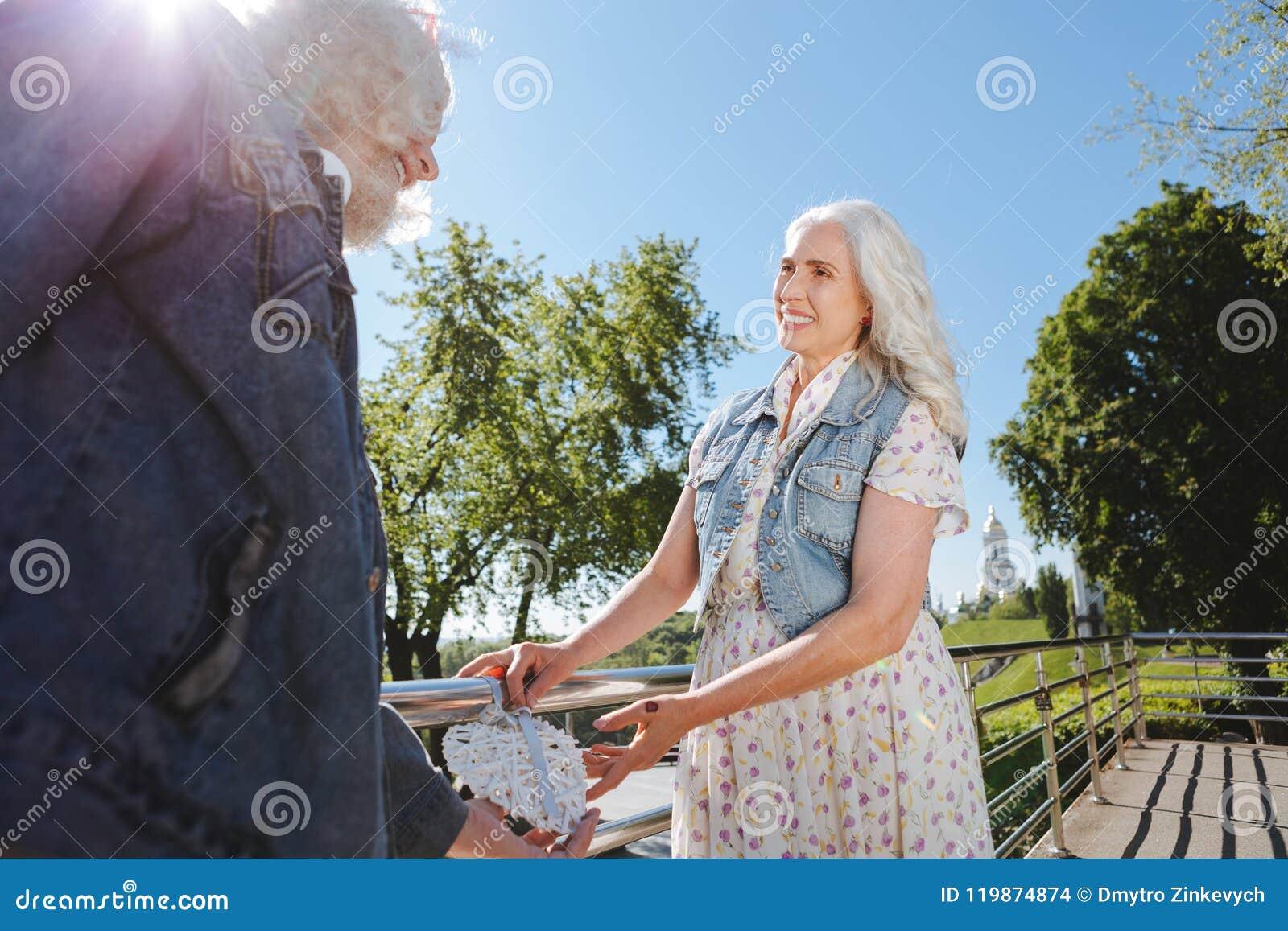 Angenehme Greisin, die zu ihrem Ehemann lächelt