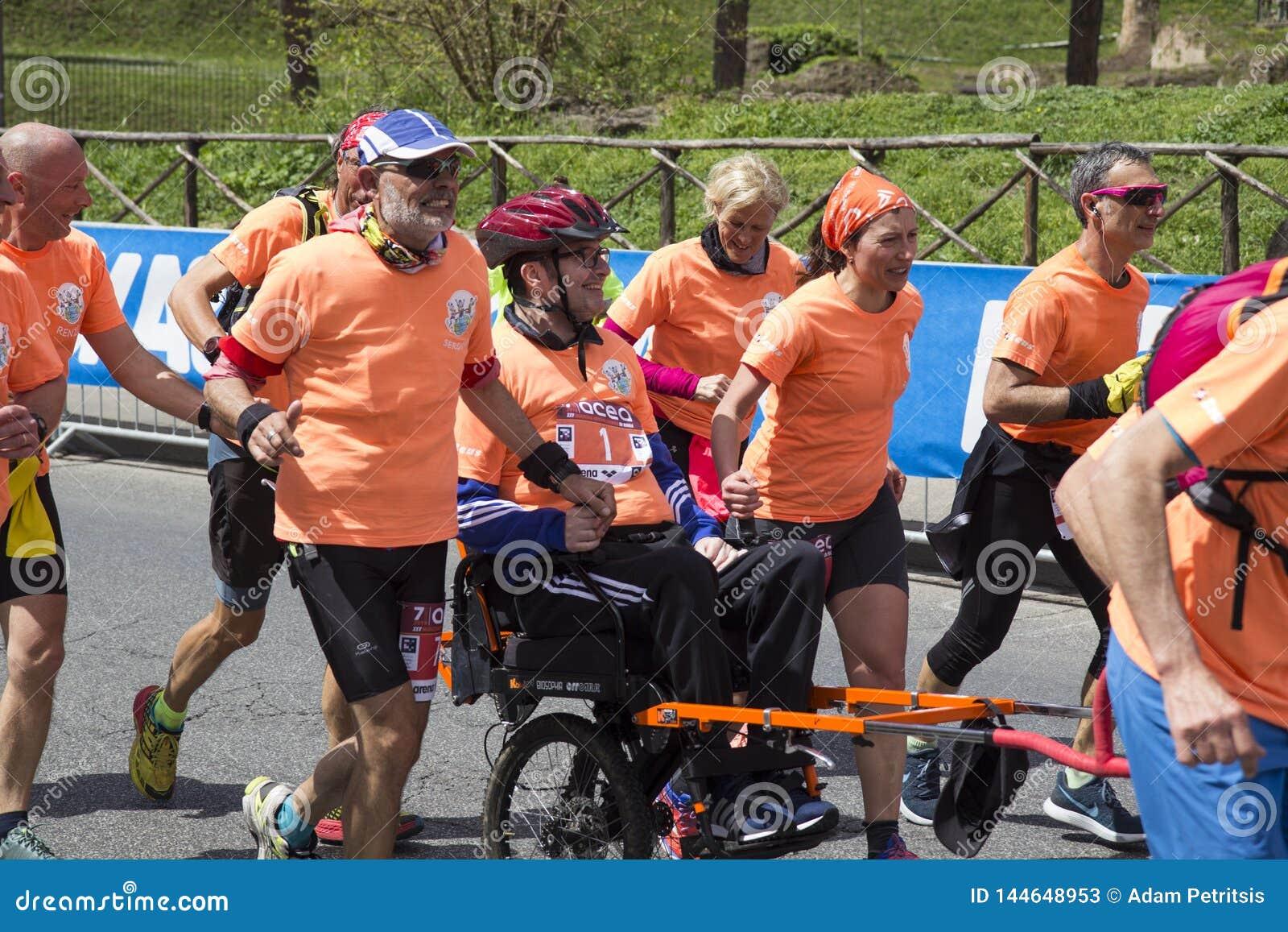 Anges fonctionnants portant un homme dans le fauteuil roulant dans la course de marathon de Rome de 2019