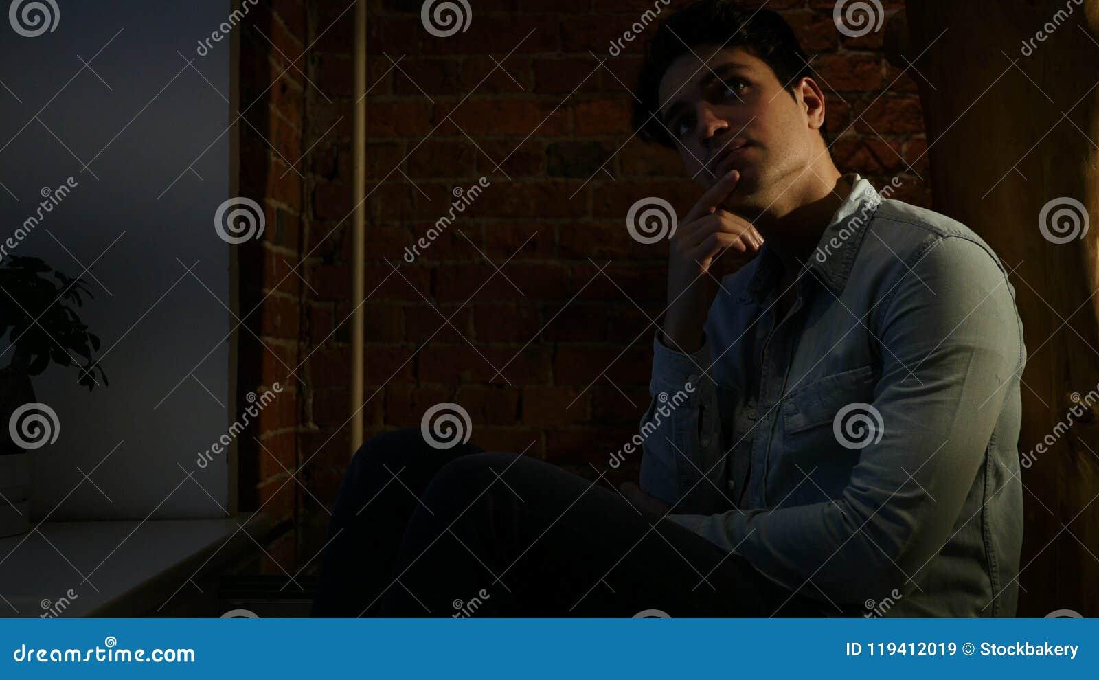 Angespannter Mann, der an die Probleme sitzen nachts, Dachboden denkt