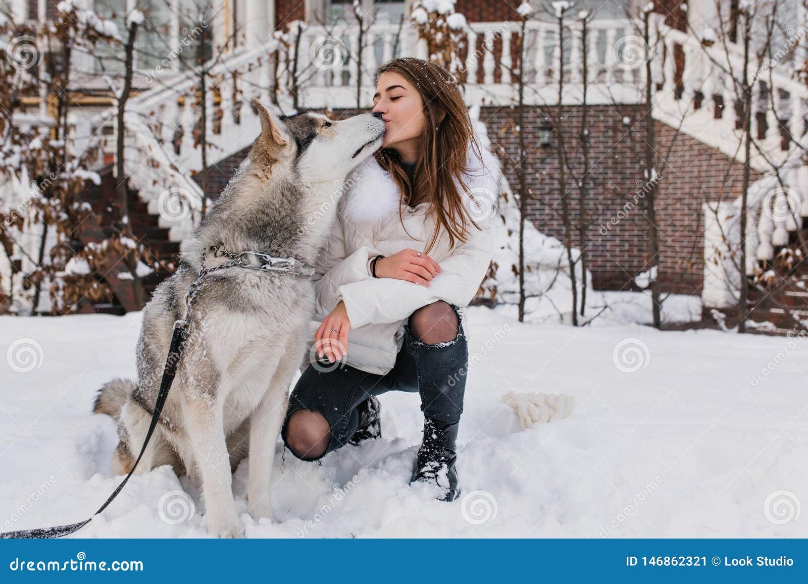 Angesporntes Mädchen in der warmen Kleidung den Wintertag im Freien verbringend, spielend mit Haustier im Yard Porträt der stilvo