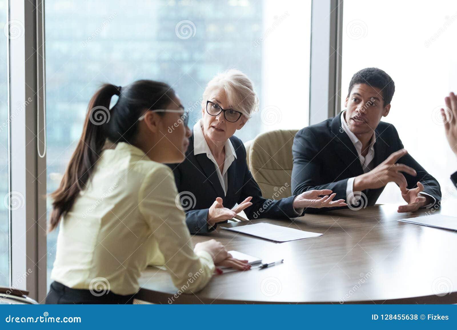 Angestellte diskutieren beschuldigen Kollegen während der Generalversammlung