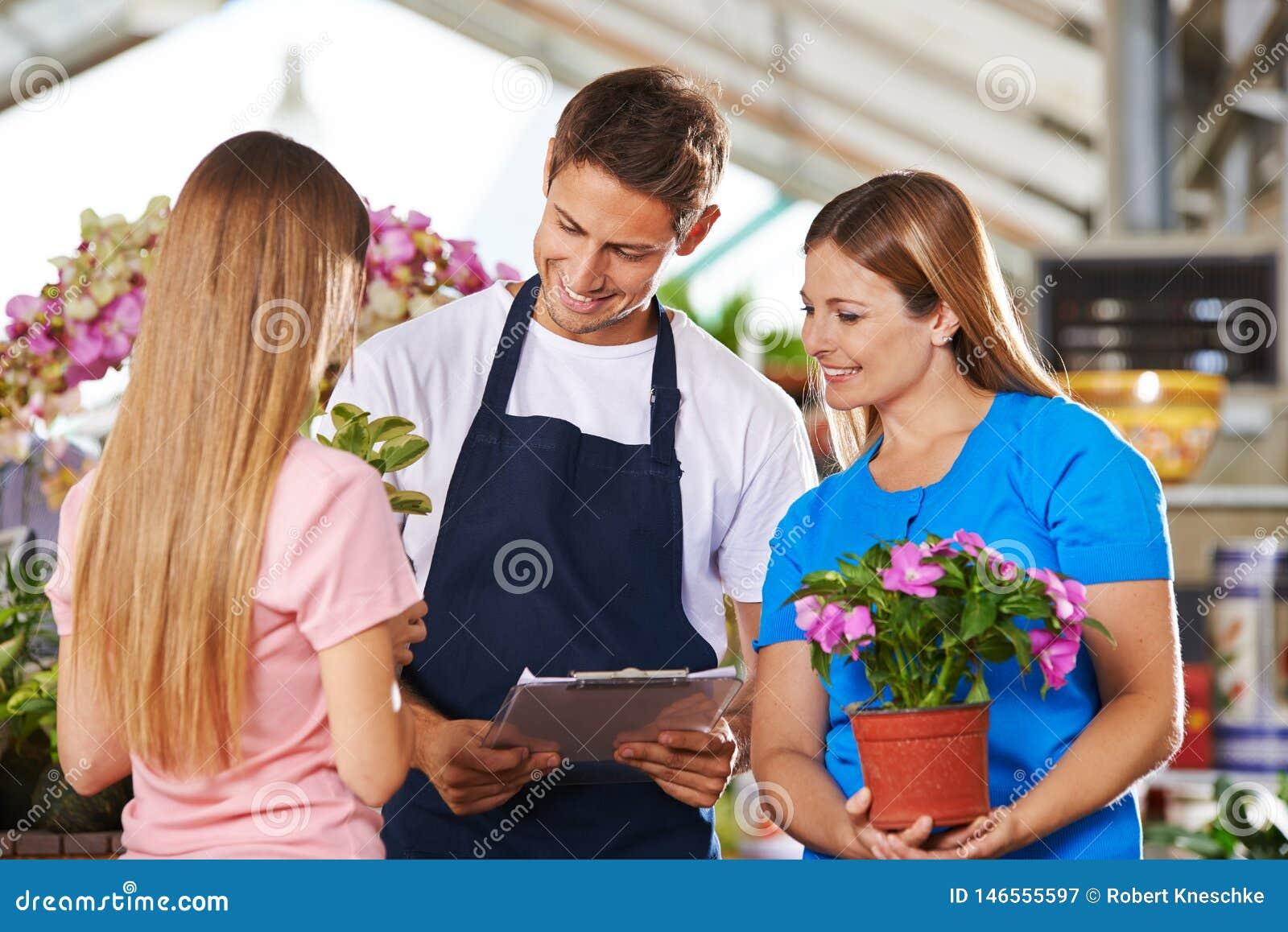 Angestellte im Blumenladen mit Rat von den Kunden