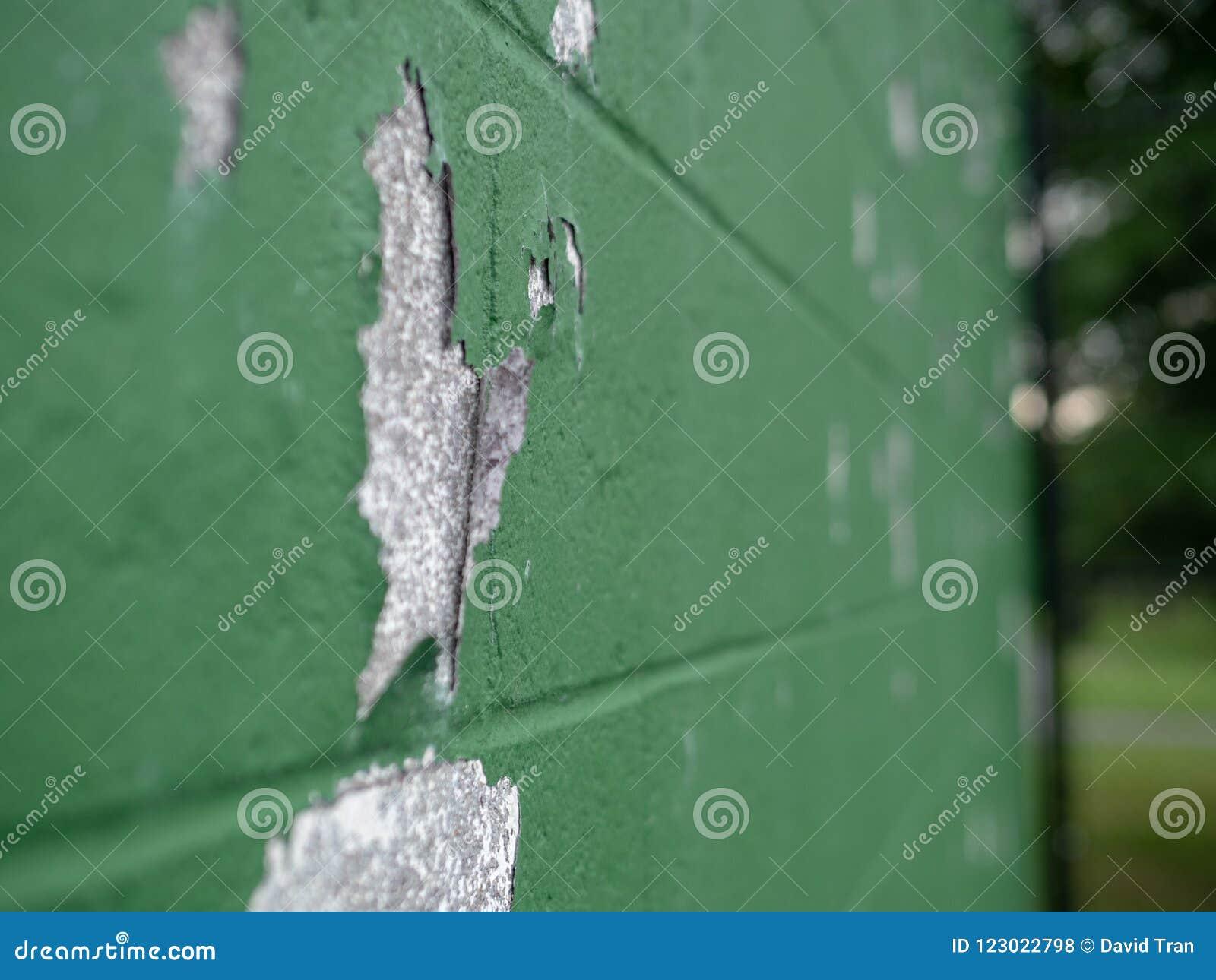 Angled взгляд краски слезая зеленой стены в outdoors