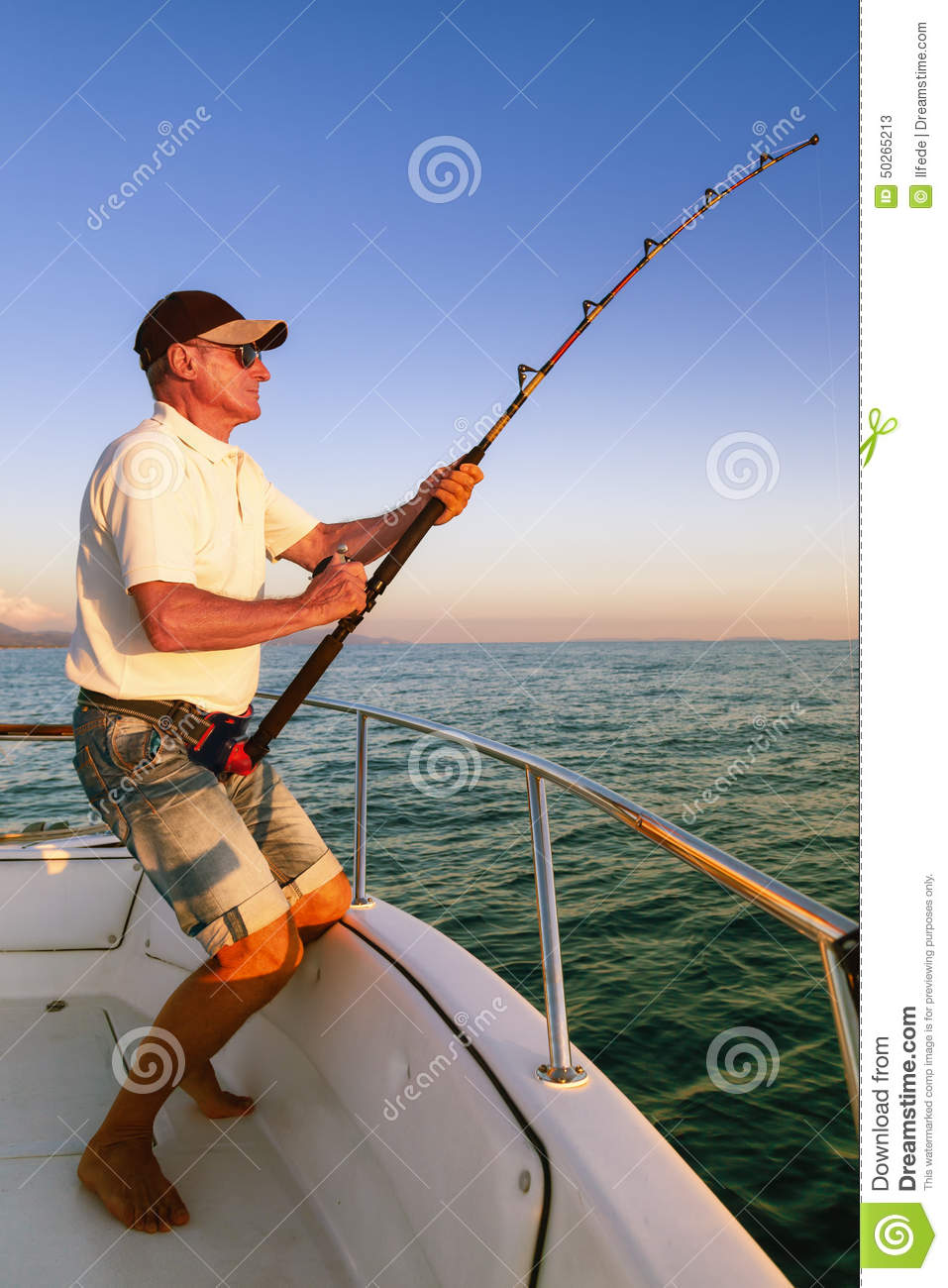 Angler fisherman fighting big fish from the boat