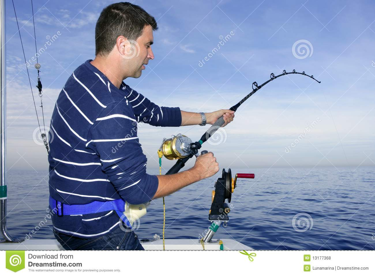 Angler fisherman fighting big fish rod and reel stock for How many fishing rods per person in texas
