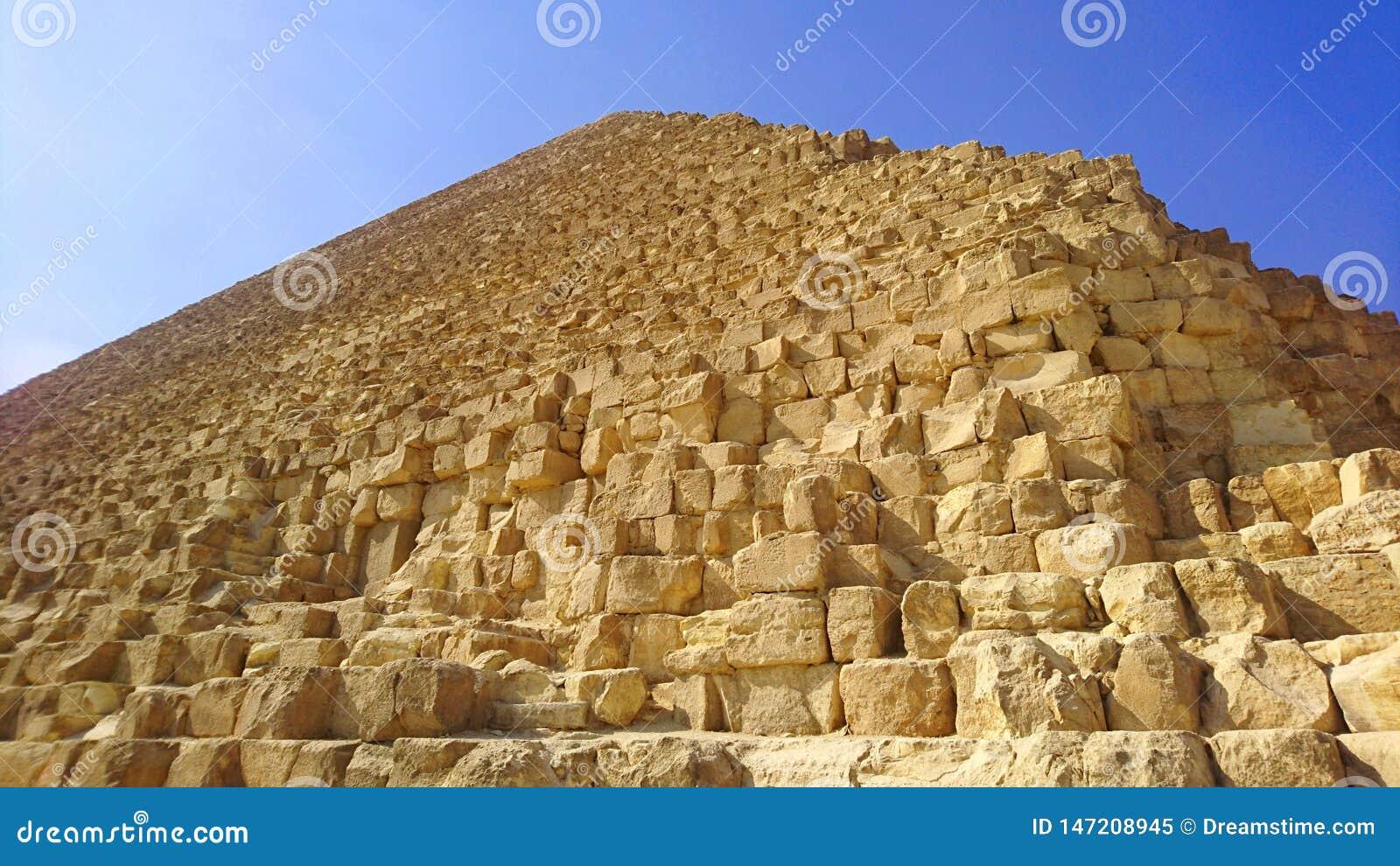 Angolo basso vicino di grande piramide sotto i cieli blu a Giza, Egitto