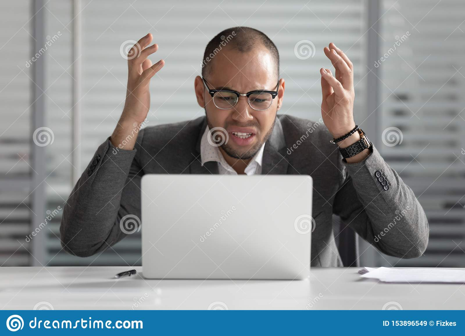 Angry african business man using laptop mad about computer problem