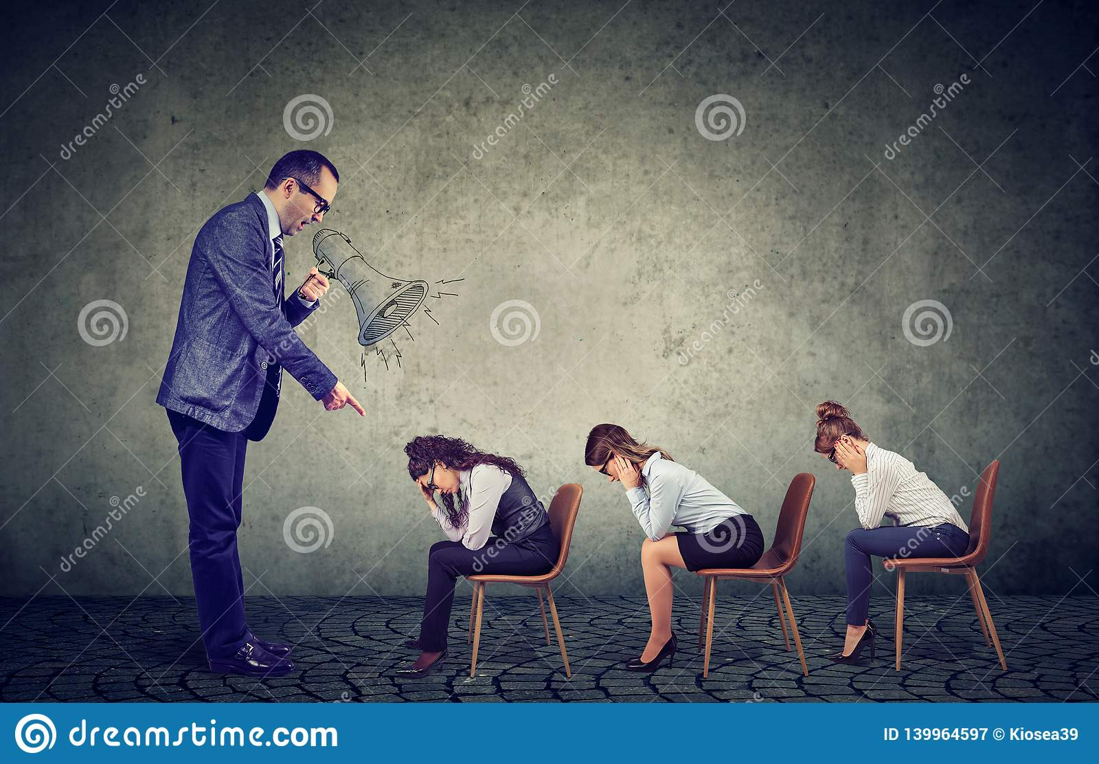 Angry boss screaming in megaphone giving orders to sad looking down female employees