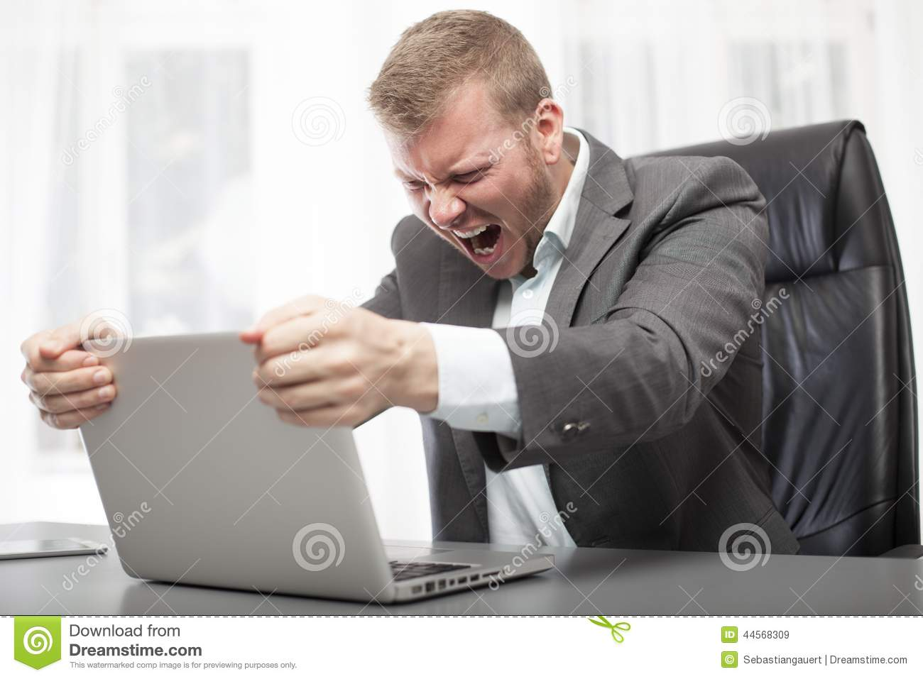 Angry businessman shaking his laptop computer