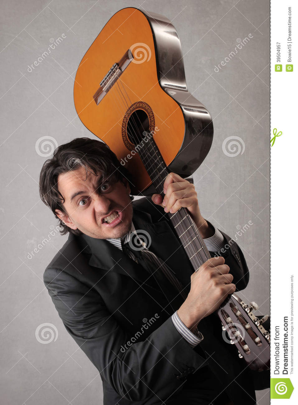 Angry businessman trying to break the guitar