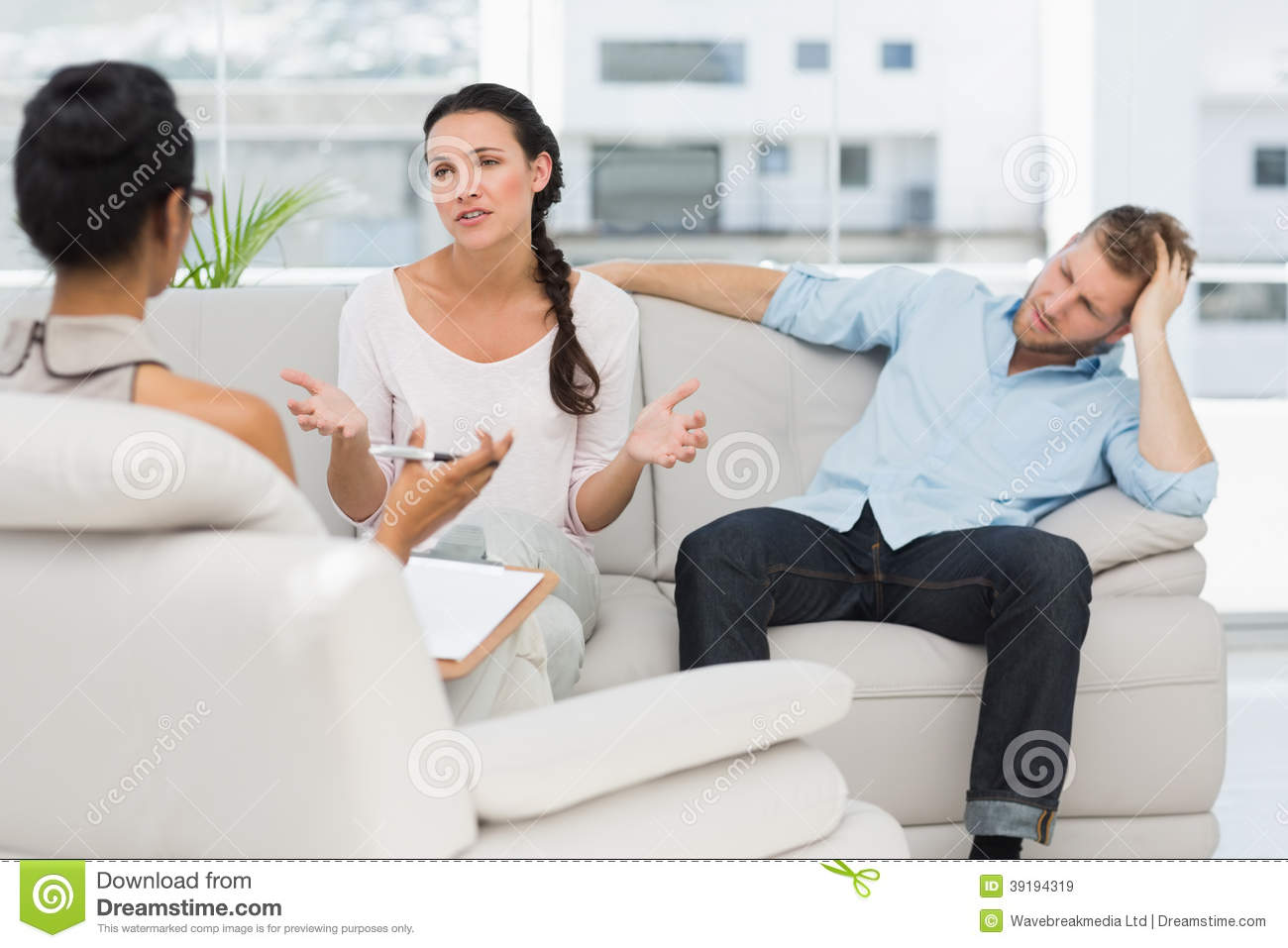 Angry Couple Sitting On Couch Talking To Therapist Stock Image