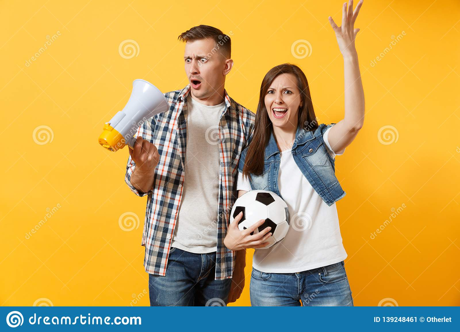 Angry fun expessive couple, woman man football fans screaming, cheer up support team with soccer ball, megaphone