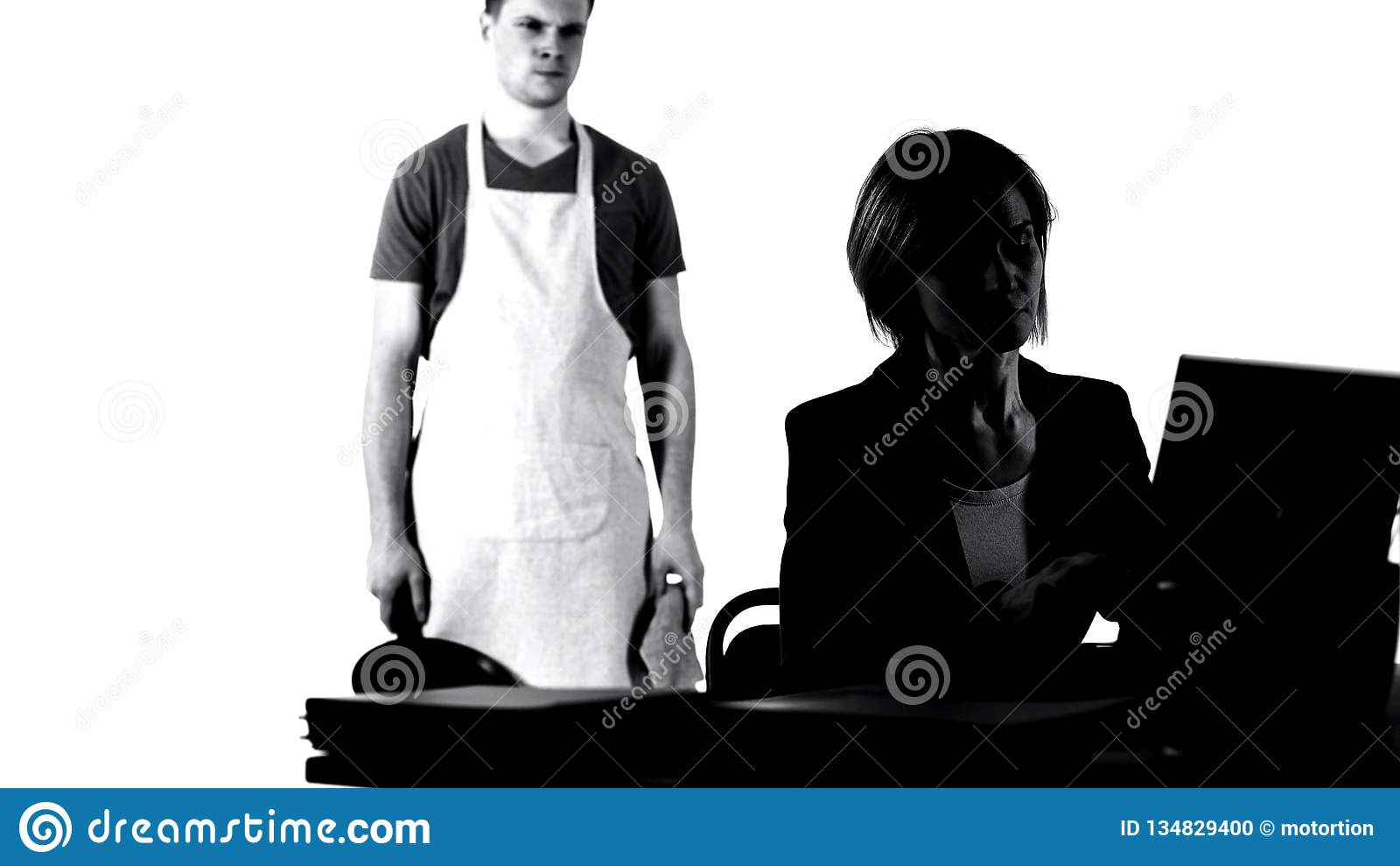 Angry husband with pan looking at working business wife, house chores tiredness