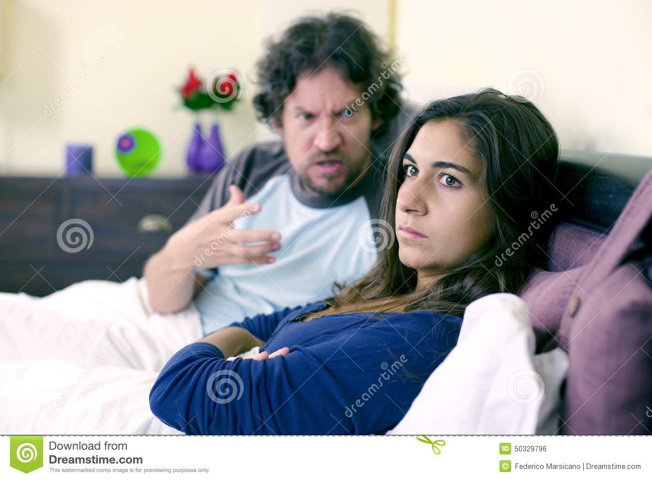 Angry husband shouting to wife in bed not listening. Angry Husband Shouting To Wife In Bed Not Listening Stock Photo