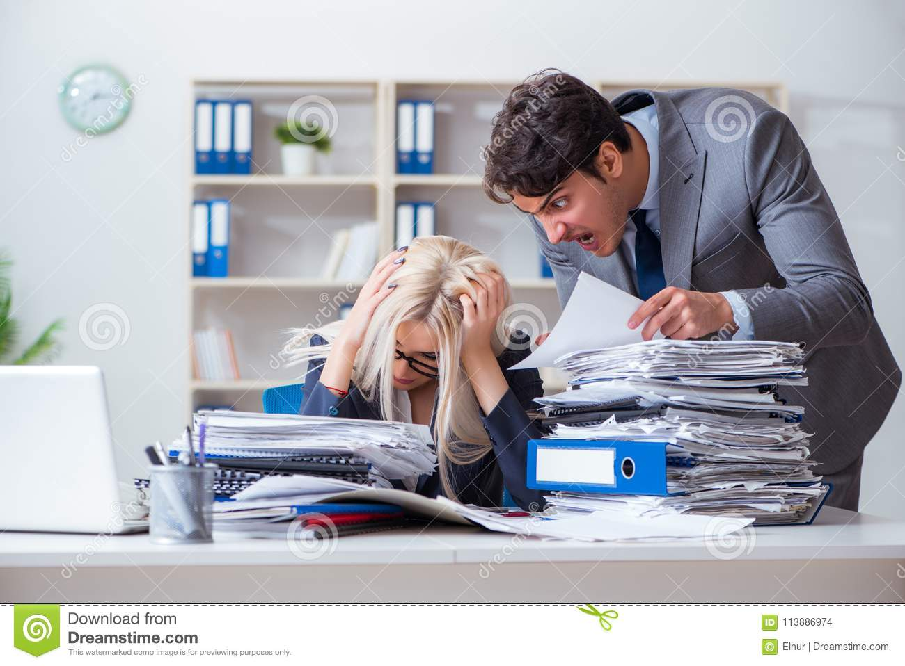 The angry irate boss yelling and shouting at his secretary employee