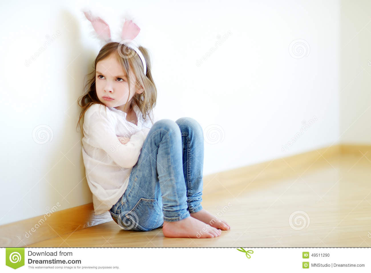 Very angry little girl wearing bunny ears sitting on a floor at home.