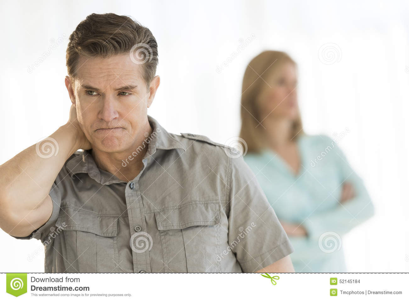 Angry Man Looking Away With Woman In Background At Home ...