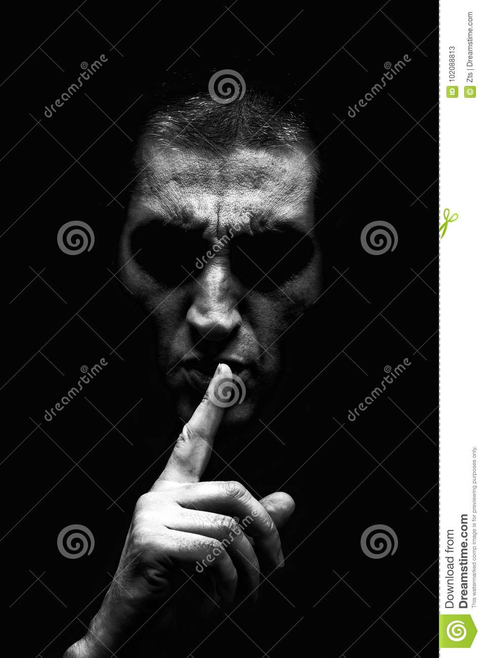 Angry mature man with an aggressive look making the silence sign in a threatening and creepy way