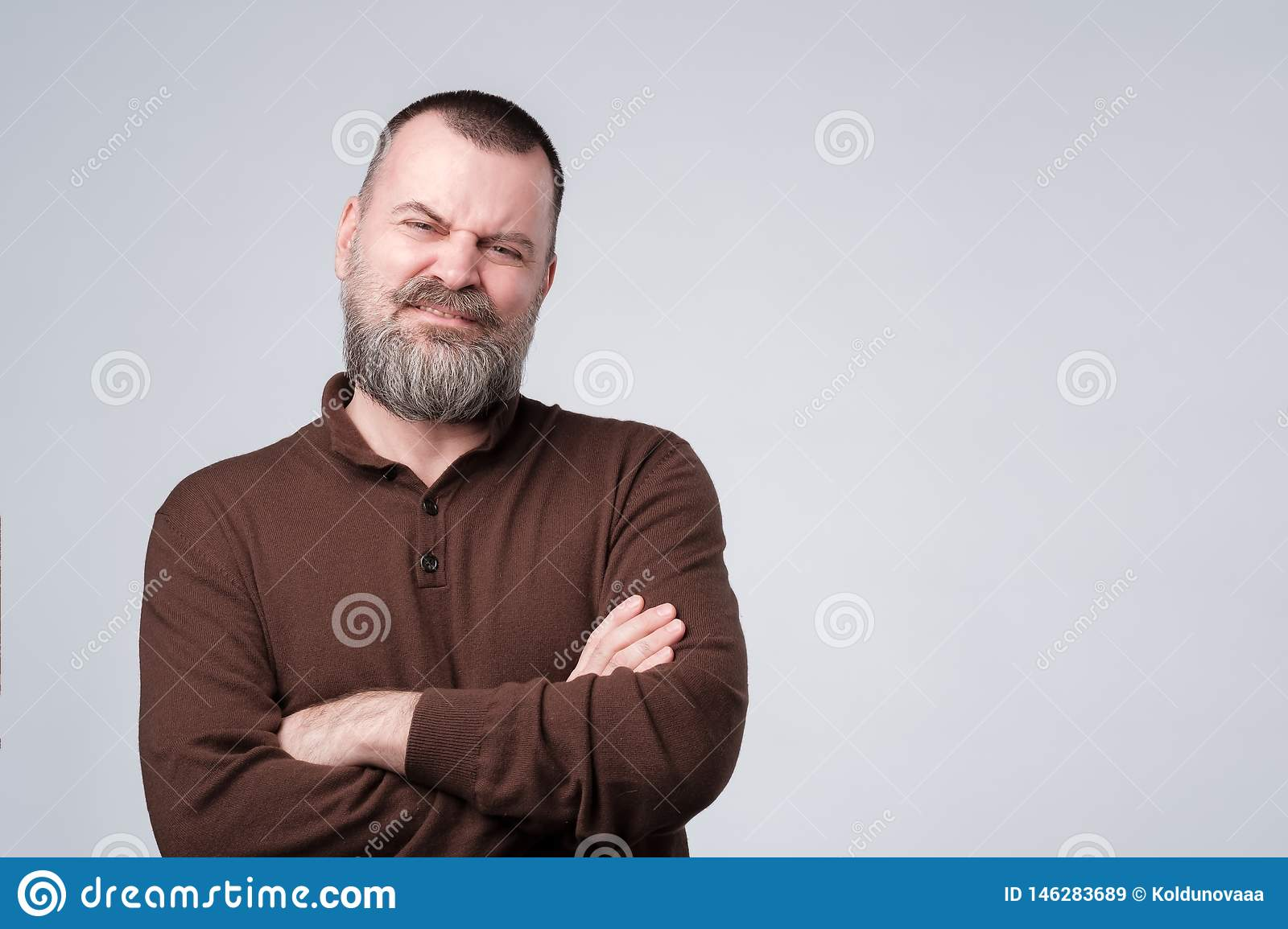 Angry, off mature man with arms crossed folded.