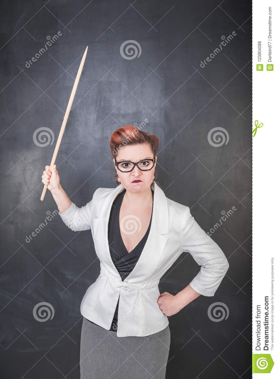 Angry teacher with pointer on the chalkboard background