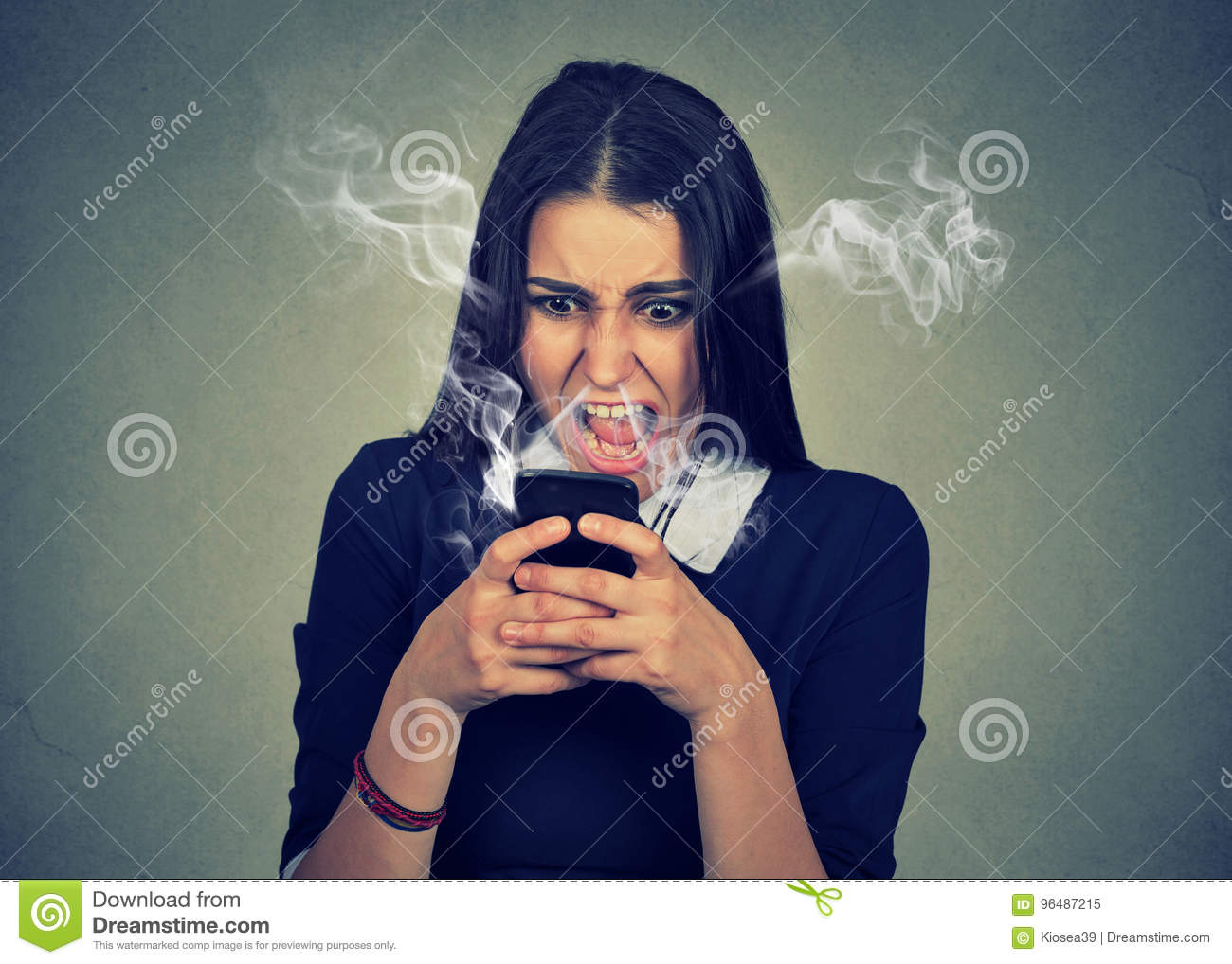 Angry woman shouting at her cell phone, enraged with bad service