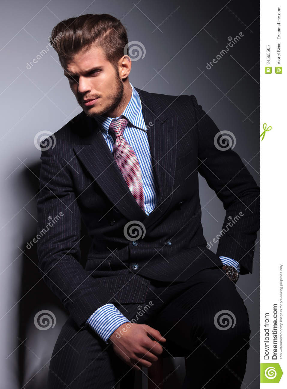 Angry Young Business Man In Classic Suit And Tie Sitting