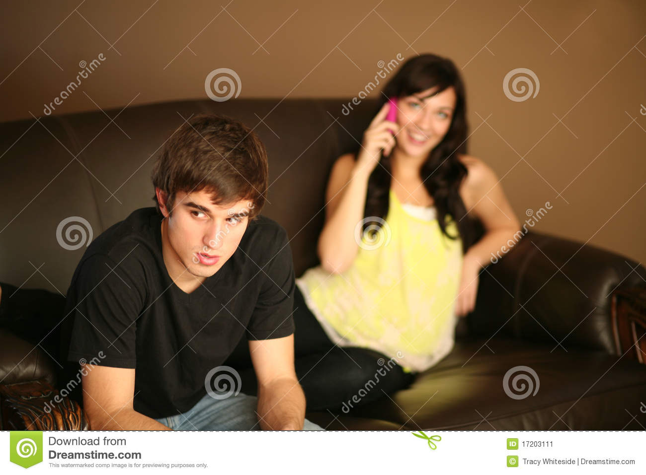 Angry young man ignored by girlfriend on phone
