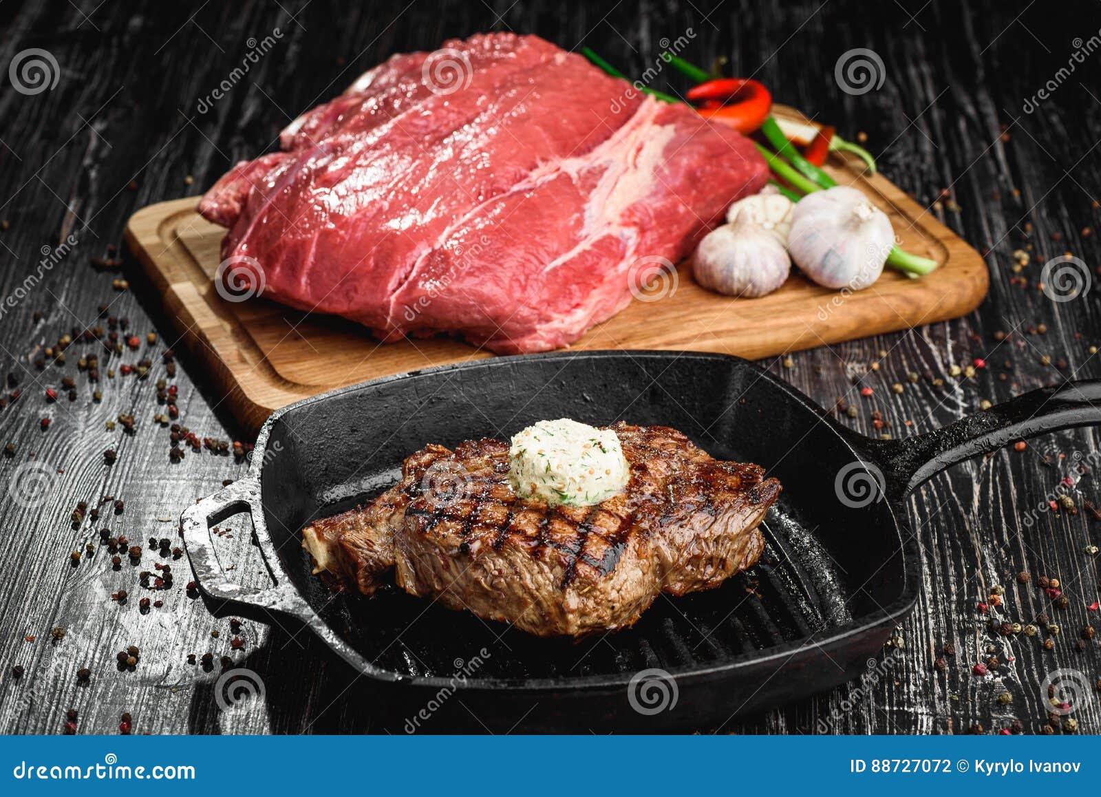 Angus Steak noir grillé sur la casserole de fer de gril sur le fond noir en bois avec cru