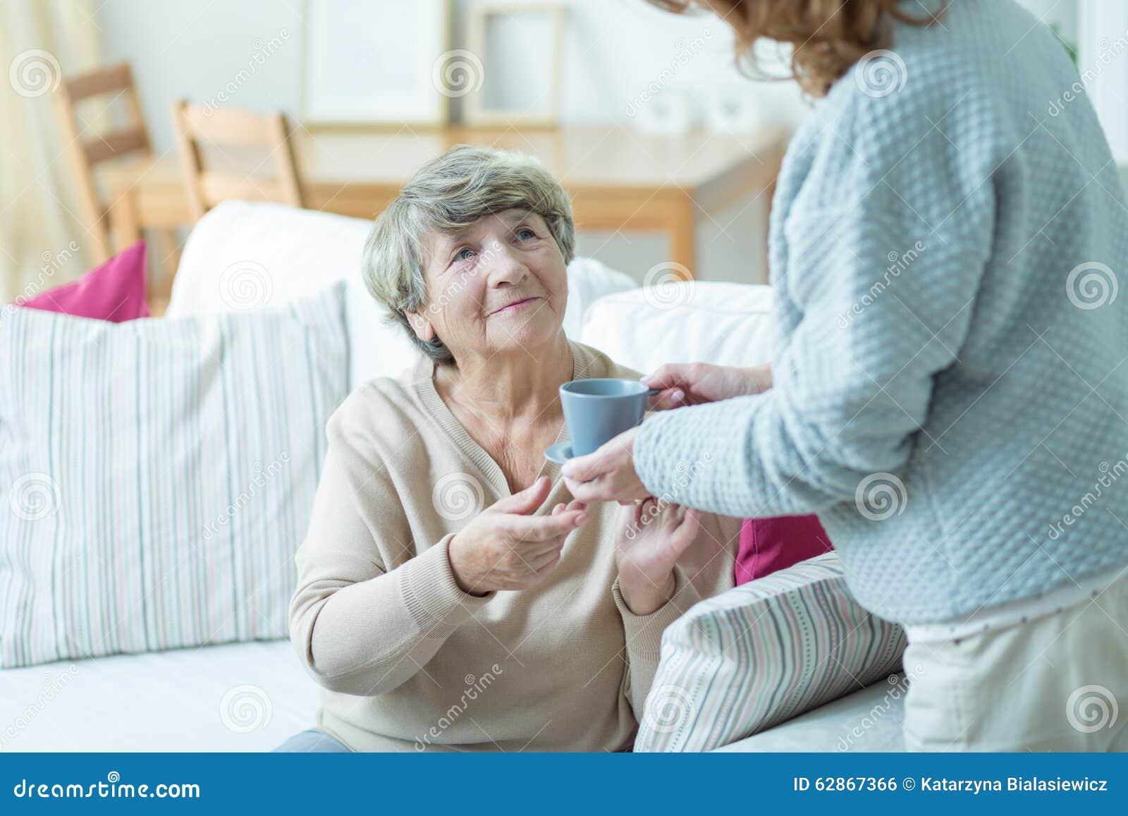 Anhörigvårdare som ger kaffe för äldre kvinna