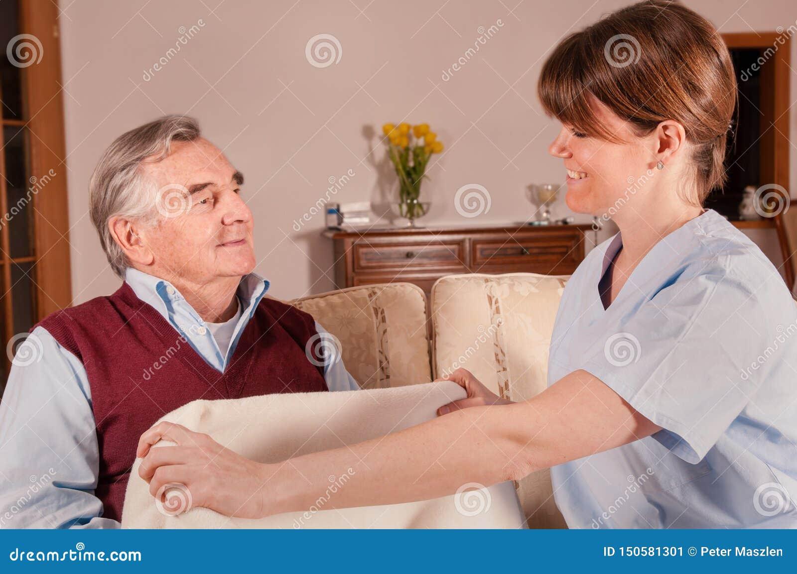 Anhörigvårdaren ger filten till den lyckliga pensionären